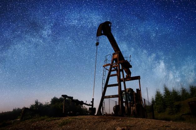 Sylwetka pompy olejowej pompuje ropę naftową na polu naftowym w nocy pod niebem z gwiazdami.
