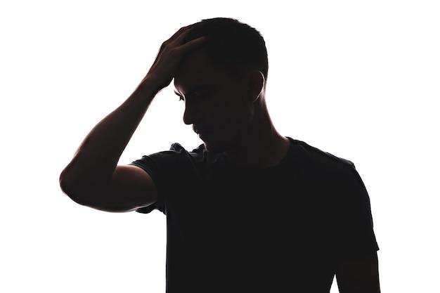 Sylwetka portret kaukaski mężczyzna zamyślony wygląd, widok z przodu trzymając głowę ręką, poza homer patrząc w dół, na białym tle