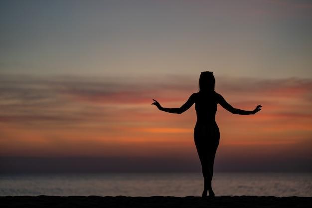 Sylwetka portret kobiety na sobie bikini na plaży, złoty moment zachodu słońca. koncepcja wakacje i podróże.
