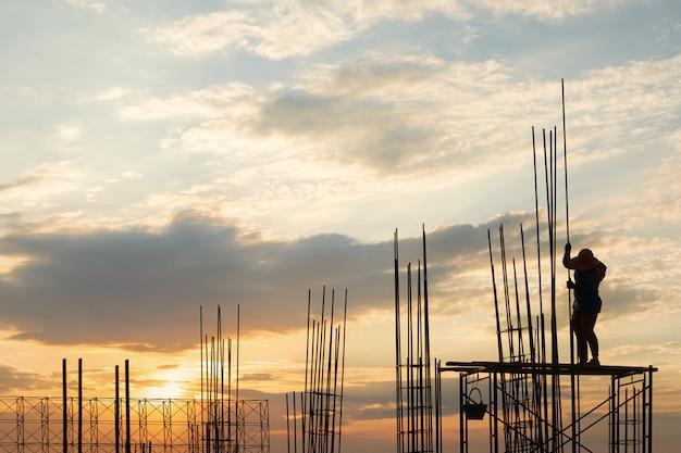 Sylwetka pracownik na bezpieczeństwo stojaku od wysokości ziemi i stalowego prącia przy budową.