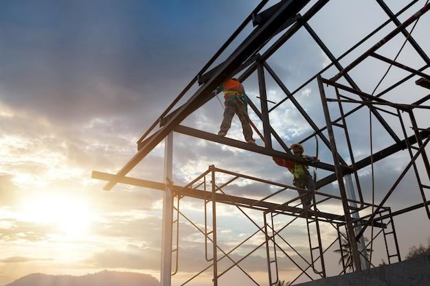 Sylwetka pracownika budowlanego na konstrukcji dachu w budowie, koncepcja wysokość wyposażenia bezpieczeństwa.