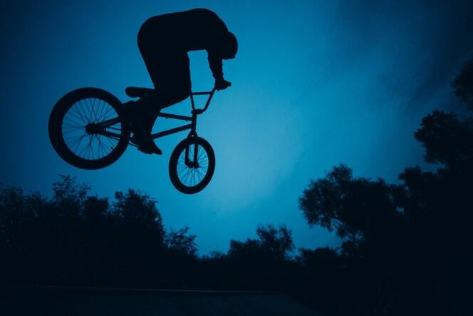 Sylwetka profesjonalnego rowerzysty młodego sportowca z rowerem bmx skaczącym w skateparku