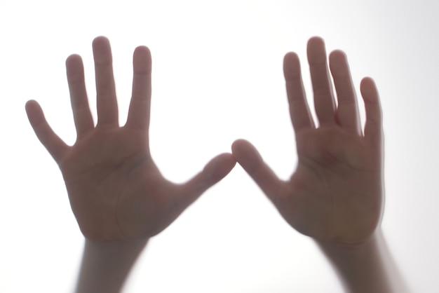 Sylwetka przestraszony chłopiec stoją za szklanymi drzwiami. dzieciak pokazując dwie ręce. tło reprezentujące niebezpieczeństwo, strach, pomoc, nawiedzenie, przerażenie i panikę. problemy nastolatków, koncepcja negatywnych emocji.
