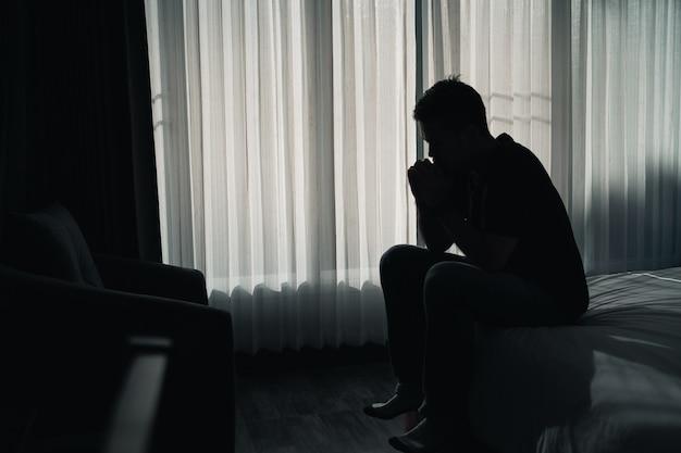 Sylwetka przygnębiony mężczyzna smutno siedzi na łóżku w sypialni, pojęcie depresji