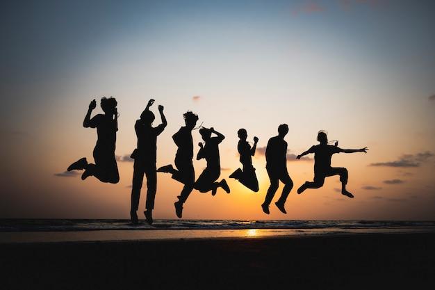 Sylwetka przyjaciela skaczącego nad morzem o zachodzie słońca