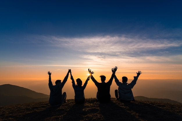 Sylwetka przyjaciół wstrząsnąć ręce i siedząc razem w zachód szczęścia
