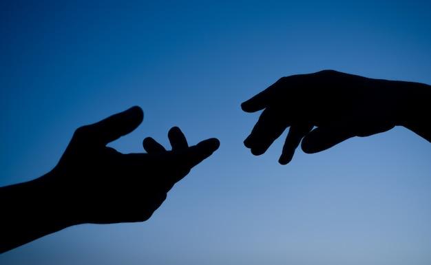 Sylwetka rąk. niebo. zachód słońca. sylwetka rąk na tle nieba. koncepcja opieki i wsparcia.