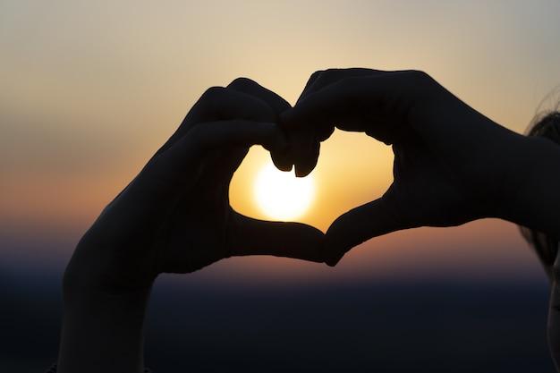 Sylwetka rąk tworzących serce o zachodzie słońca