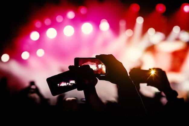 Sylwetka rąk za pomocą smartfonów do robienia zdjęć i filmów podczas koncertu muzycznego na żywo.