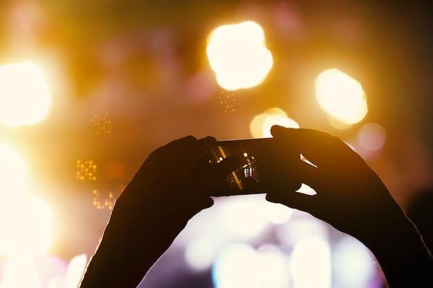 Sylwetka rąk za pomocą telefonu z aparatem do robienia zdjęć i filmów na koncercie na żywo