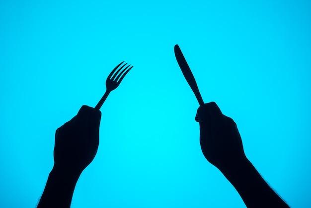 Sylwetka ręce trzymając widelec i nóż. elementy kuchenne