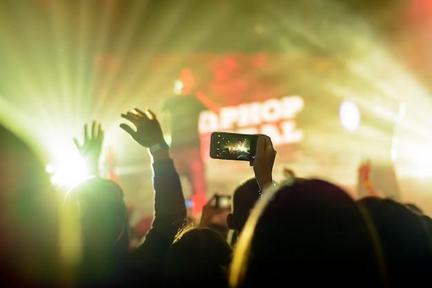 Sylwetka ręki z smartphone przy koncertem