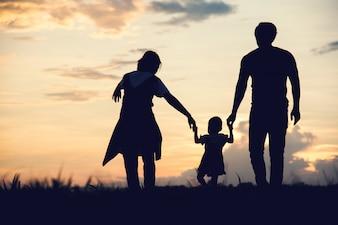 Sylwetka rodzinni szczęśliwi rodzice ma zabawę