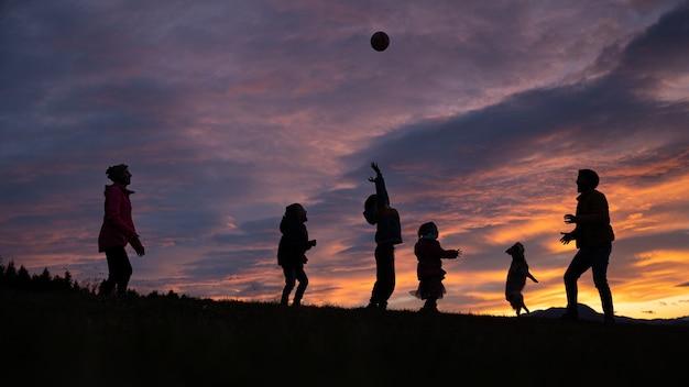 Sylwetka rodziny bawić się i bawić się na zewnątrz pod pięknym zachmurzonym niebem o zachodzie słońca.