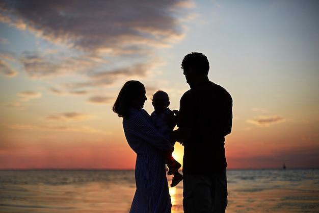 Sylwetka rodziny mama, tata dziecko o zachodzie słońca nad morzem.