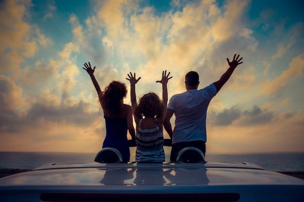 Sylwetka rodziny relaks na plaży ludzie bawią się w kabriolecie na tle błękitnego nieba letnie wakacje i koncepcja podróży
