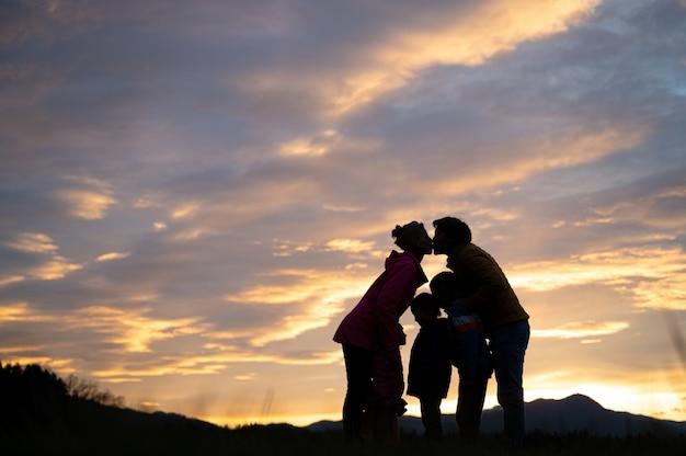 Sylwetka rodziny stojącej razem na zewnątrz pod pięknym zachmurzonym niebem o zachodzie słońca z rodzicami dając sobie nawzajem buziaka.