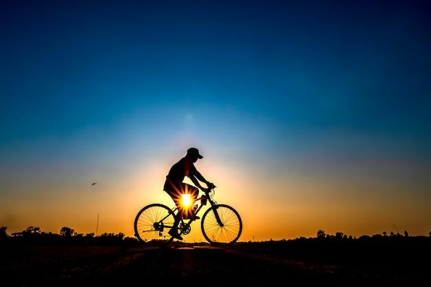Sylwetka rowerzysta w tle zachodu słońca.