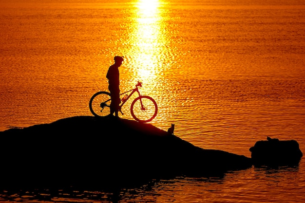 Sylwetka rowerzystów na skale na tle rzeki. zbliżenie na pomarańczowy zachód słońca.