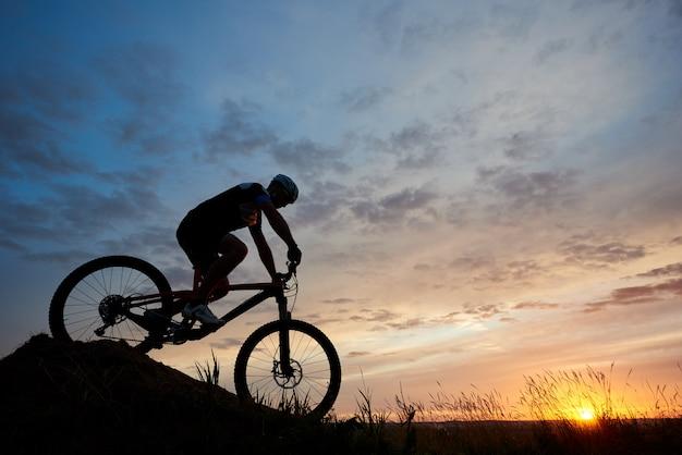 Sylwetka rowerzysty na łące