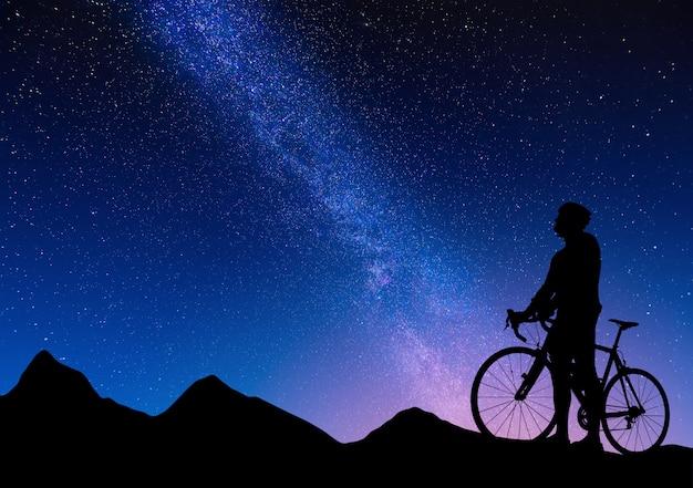 Sylwetka rowerzysty na rowerze szosowym przed drogą mleczną. piękny nocny krajobraz rowerzysty drogowego w górach na rozgwieżdżonym niebie