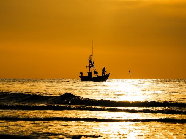 Sylwetka rybacy w łodzi na zmierzchu morzu