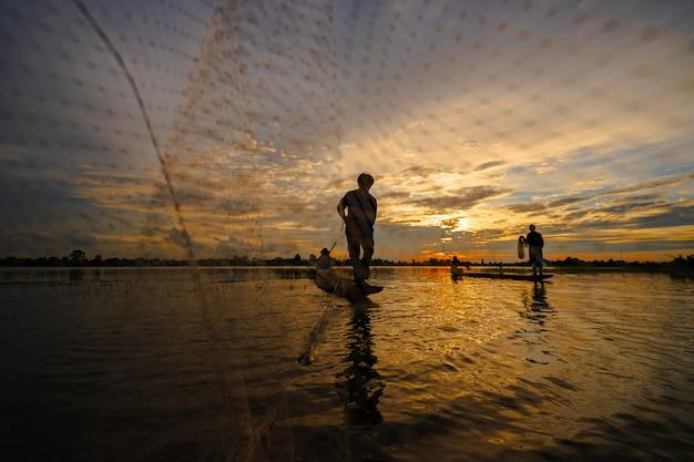 Sylwetka rybak na łodzi rybackiej z siecią na jeziorze przy zmierzchem, tajlandia