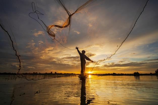 Sylwetka rybak na łodzi rybackiej z siecią na jeziorze przy zmierzchem