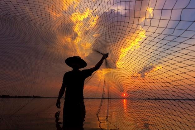 Sylwetka rybak z zachodem słońca