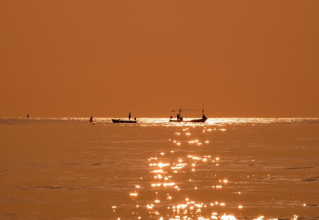Sylwetka rybaka łowiącego złote morze piękny połysk naturalny o poranku
