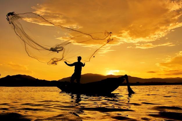 Sylwetka rybaka miotania sieć rybacka w tajlandia