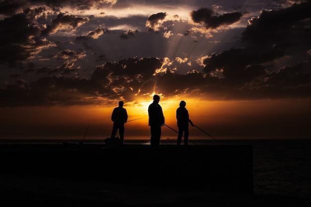 Sylwetka rybaka na plaży o zachodzie słońca