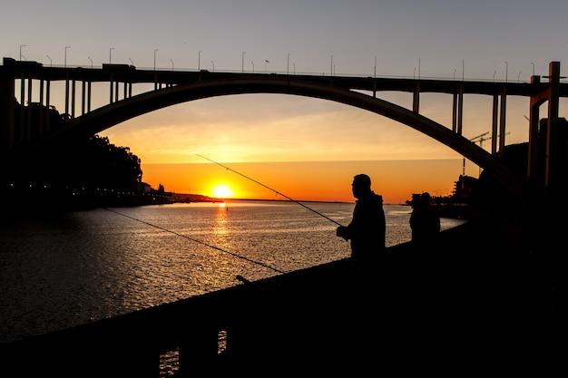 Sylwetka rybaka na zachód słońca w mieście.