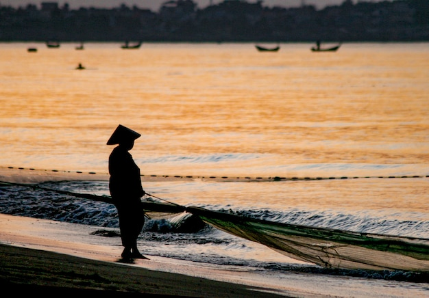 Sylwetka rybaka z łodzią na wybrzeżu
