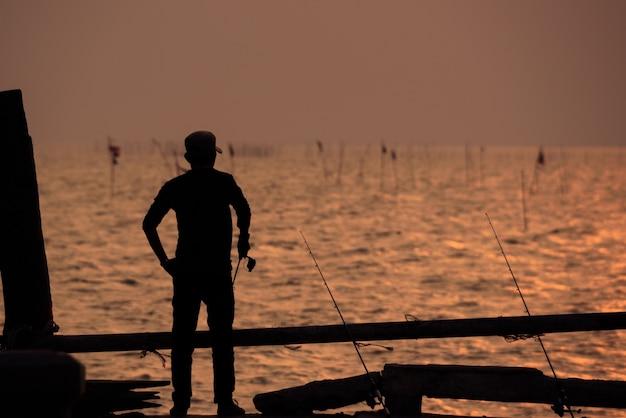 Sylwetka rybaka z nieba słońca
