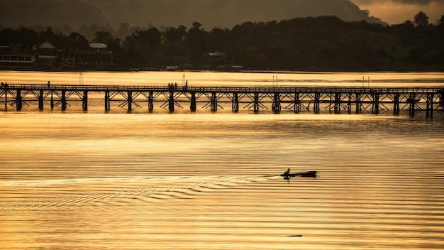 Sylwetka rybaków pływa łodzią w pobliżu mostu mon o wschodzie słońca, sangkhlaburi, kanchanaburi, tajlandia.