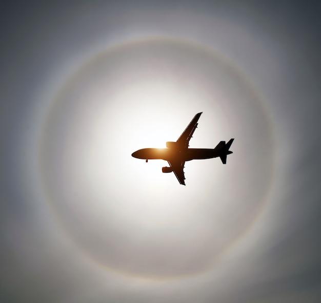 Sylwetka samolotu na niebie słońce i halo w chmurach.