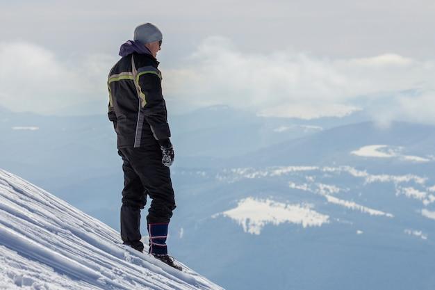 Sylwetka samotna turystyczna pozycja na śnieżnym góra wierzchołku cieszy się widok i osiągnięcie na jaskrawym pogodnym zima dniu. przygoda, zajęcia na świeżym powietrzu i koncepcja zdrowego stylu życia.