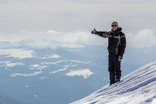 Sylwetka samotna turystyczna pozycja na śnieżnym góra wierzchołku w zwycięzca pozie z nastroszonymi rękami cieszy się widok i osiągnięcie na jaskrawym pogodnym zima dniu. przygoda, zajęcia na świeżym powietrzu, zdrowy styl życia.