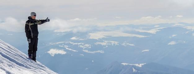 Sylwetka samotnego turysty stojącego na zaśnieżonej górze w pozie zwycięzcy z uniesionymi rękami, ciesząc się widokiem i osiągnięciami w jasny słoneczny zimowy dzień. przygoda, aktywność na świeżym powietrzu, zdrowy tryb życia.