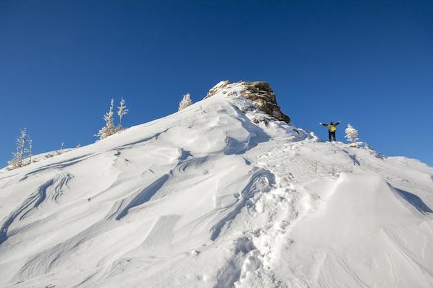 Sylwetka samotnego turysty stojącego na zaśnieżonym szczycie góry w pozie zwycięzcy z uniesionymi rękami.