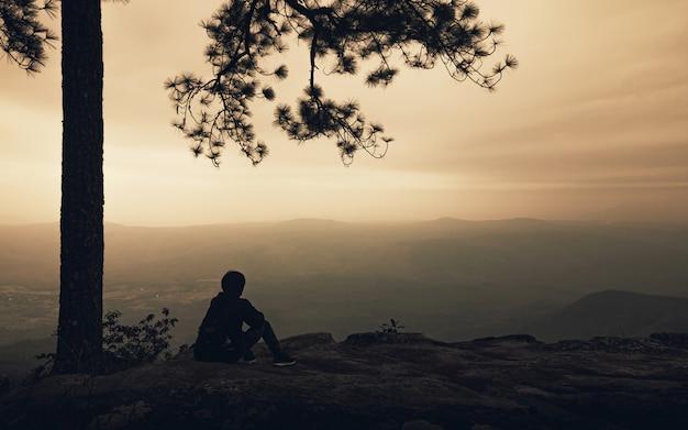 Sylwetka samotny mężczyzna siedzi pod wielkim drzewem na widoku górskim z mgłą w zmierzchu