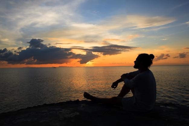 Sylwetka sceny jogi o zachodzie słońca