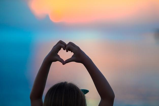 Sylwetka serca wykonane ręcznie przez dzieci o zachodzie słońca