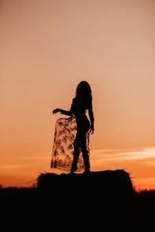 Sylwetka sexy dziewczyna w przezroczystej sukience latem o zachodzie słońca w polu na stogu siana w przyrodzie.