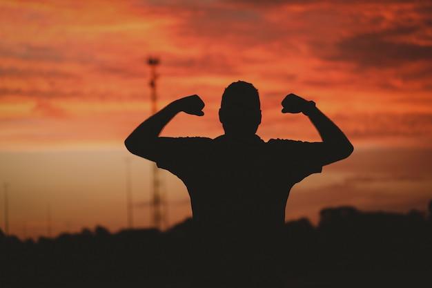 Sylwetka silnego człowieka pod zachmurzonym niebem podczas złotego zachodu słońca