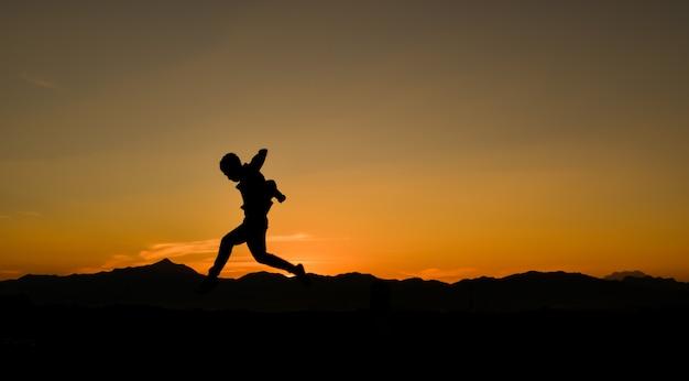 Sylwetka skaczącego człowieka o zachodzie słońca