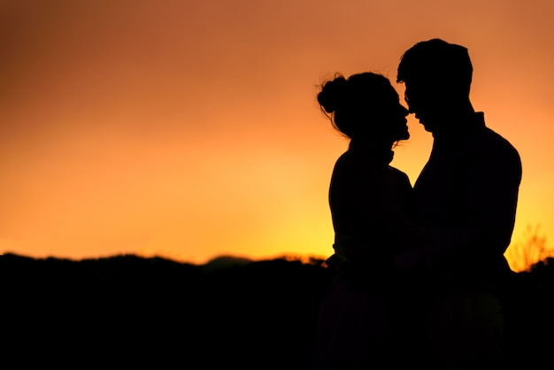 Sylwetka ślubu para zakochanych całuje i trzymając rękę razem podczas zachodu słońca na tle wieczornego nieba