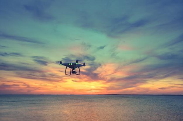 Sylwetka śmigłowcowego trutnia quad latający w niebie