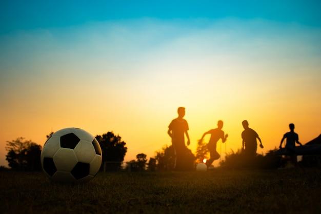 Sylwetka sport akcji na świeżym powietrzu z grupy dzieci, zabawy grając w piłkę nożną
